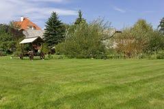 在村庄附近的理想的草草甸 库存照片