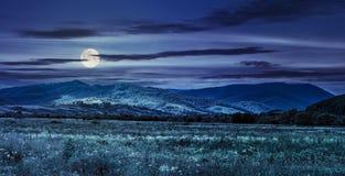 在村庄附近的草甸山坡的在晚上 免版税库存图片