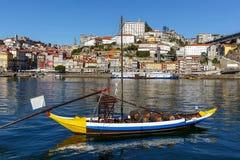 在杜罗河河的传统木小船运输的与城市的酒波尔图市,葡萄牙背景的  免版税库存照片