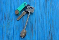 在束的三把门钥匙在一张蓝色桌上 免版税图库摄影
