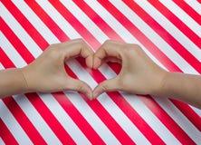 在条纹图形红色&白色placemats上把放的两手心形  免版税库存照片