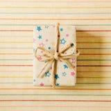 在条纹织品背景的礼物盒 库存照片