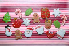 在条纹背景顶视图的圣诞节曲奇饼 各种各样的类型圣诞节姜饼曲奇饼舱内甲板位置 圣诞节字符曲奇饼 库存图片