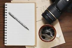 在杯子、笔记本和一台DSLR照相机的咖啡在桌上 库存图片