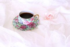 在杯子和一点桃红色花的早晨热的coffe在白色缎背景 特写镜头,顶视图 季节性,早晨咖啡 免版税图库摄影