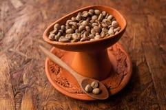 在杯子和匙子的咖啡豆在木桌上 库存图片