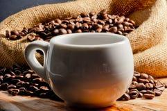 在杯子和咖啡豆的精神充沛的饮料 库存图片