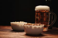 在杯子和快餐的啤酒光 库存图片