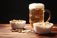 在杯子和快餐的啤酒光 免版税库存照片