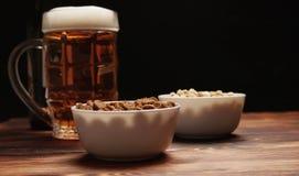 在杯子和快餐的啤酒 免版税库存图片