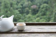 在杯子和杯子的白色茶在与绿色自然backgro的木桌上 免版税库存照片
