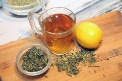 在杯子和草本的茶在碗 免版税库存图片