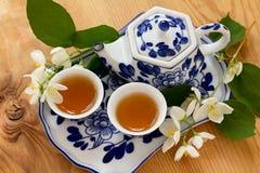 在杯子和陶瓷茶壶的茉莉花绿茶在盘子 库存图片