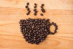 在杯子形状的咖啡豆 免版税库存照片