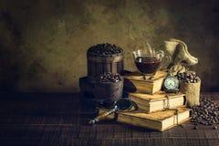 在杯子玻璃在旧书和时钟葡萄酒的咖啡在年迈的木头 免版税库存照片