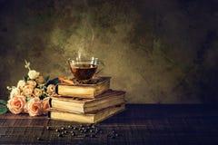 在杯子玻璃的咖啡在旧书和在年迈的木地板上上升了 图库摄影
