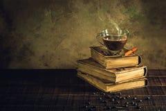 在杯子玻璃的咖啡在旧书和年迈的木地板 免版税库存照片