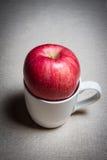 在杯子的一个苹果 库存图片