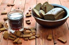 在杯子的俄国啤酒在一个木桌和黑麦面包上 免版税库存照片
