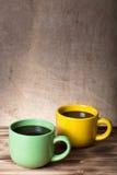 在杯子的咖啡在一defocused粗麻布backgr对面的木桌上 免版税图库摄影