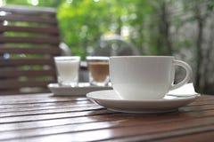 在杯子的咖啡在早晨时间的木桌上 库存图片