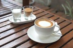 在杯子的咖啡在早晨时间的木桌上 库存照片