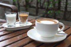 在杯子的咖啡在早晨时间的木桌上 免版税图库摄影
