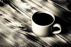 在杯子的咖啡在背景的木桌上 定调子 库存图片