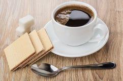 在杯子的咖啡在茶碟、匙子、奶蛋烘饼和多块的糖 免版税库存照片