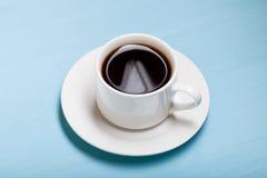 在杯子的咖啡在蓝色木桌上 库存图片
