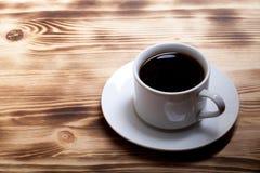 在杯子的咖啡在轻的木桌上 库存图片