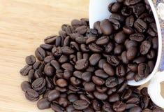 在杯子的咖啡豆在木头 免版税库存照片