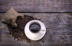 在杯子的咖啡,咖啡豆,在木背景的香料 库存照片