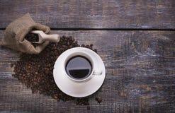 在杯子的咖啡,咖啡豆,香料,以心脏的形式曲奇饼在木背景 免版税库存照片