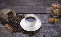 在杯子的咖啡,咖啡豆,香料,以心脏的形式曲奇饼在木背景 免版税库存图片