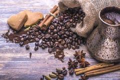 在杯子的咖啡,咖啡豆,香料:桂香,豆蔻果实,茴香,在木背景的曲奇饼 免版税库存图片