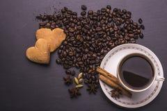 在杯子的咖啡,咖啡豆,香料:桂香,豆蔻果实,茴香,曲奇饼在黑背景 免版税库存照片