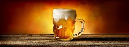 在杯子的啤酒在桌上 库存照片
