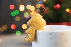 在杯子的圣诞树曲奇饼热奶咖啡 库存照片