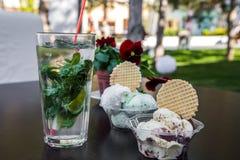 在杯子的在桌上的冰淇凌和饮料 库存照片