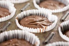 在杯子的未加工的巧克力杯子蛋糕混合物结块纸准备好烘烤 免版税库存图片