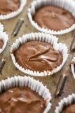 在杯子的未加工的巧克力杯子蛋糕混合物结块纸准备好烘烤 图库摄影