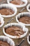 在杯子的未加工的巧克力杯子蛋糕混合物结块纸准备好烘烤 库存图片