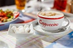 在杯子的热奶咖啡题字 库存照片