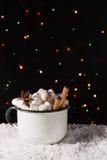 在杯子的热巧克力用蛋白软糖和香料在雪有圣诞灯背景 复制空间 免版税库存图片