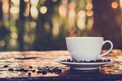 在杯子的热的咖啡在老木桌上有迷离深绿自然背景 免版税库存照片