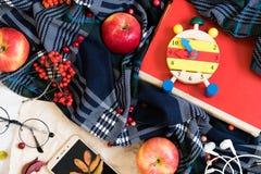 在杯子的热的咖啡有格子花呢披肩或围巾的,有耳机的手机,葡萄酒桌表面上的秋天叶子,有选择性 免版税库存图片