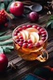 在杯子的热的苹果蔓越桔桂香茶在木桌上 免版税库存图片