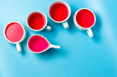 在杯子的红色清凉茶在蓝色背景 库存图片