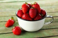 在杯子的草莓在绿色木背景 图库摄影